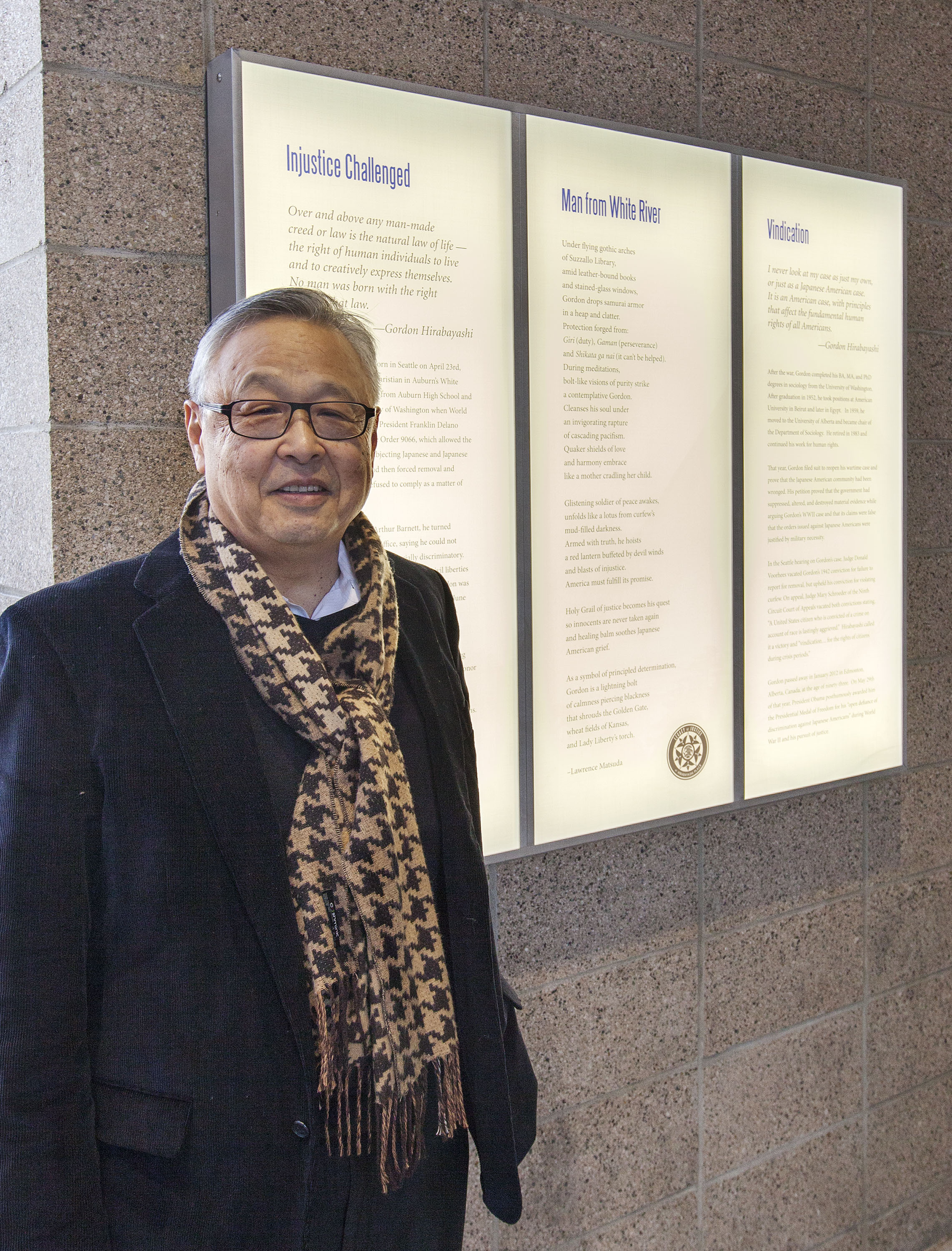 Lawrence Y. Matsuda PH.D stands with his work outside of the Gordon Hirabayashi Building in Downtown Seattle.